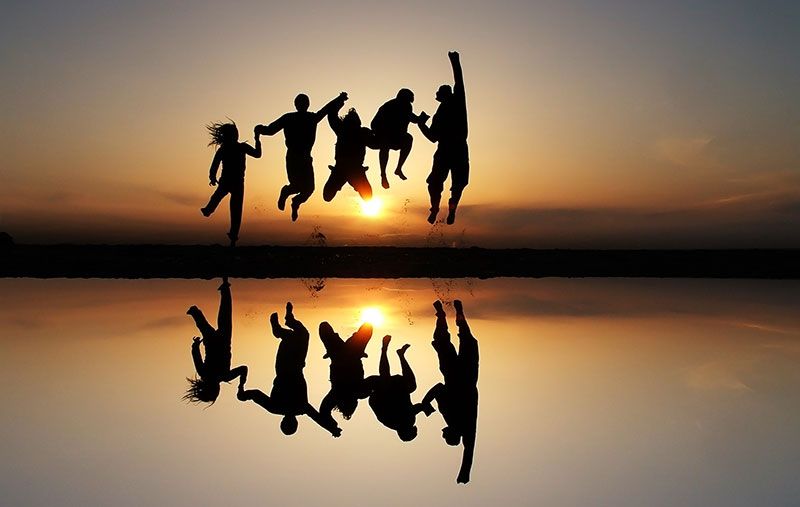 People jumping in front of a sunset