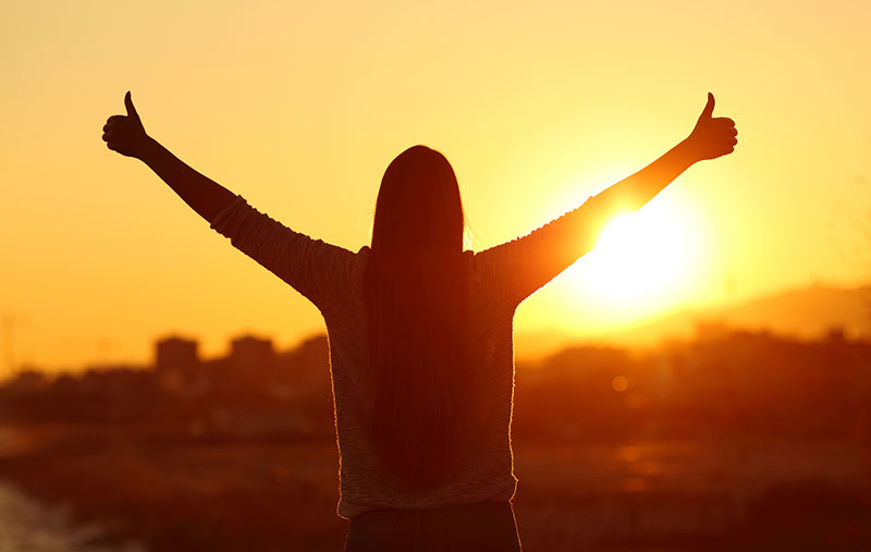 Woman giving thumbs up while looking at sunrise
