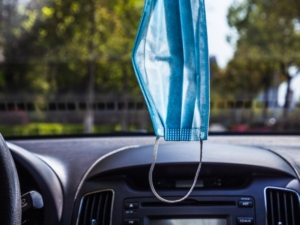 mask hanging in car from rearview mirror shows adaptability in the workplace