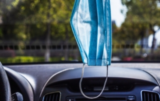 mask hanging in car from rearview mirro