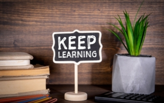 sign that says keep learning on a desk to indicate continuous improvement